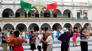Couples dance in Vera Cruz, Mexico with government buildings decorated for Independence Day celebrations.