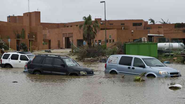 Cars sit in a flooded street in San Jose del Cabo Monday, after Hurricane Odile knocked down trees and power lines in Mexico's Baja California peninsula.
