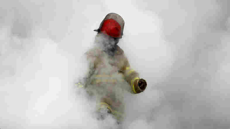 An Afghan firefighter emerges from the smoke from a fire in a Kabul clothing market in 2012. The fire department is remarkably professional in a city where few institutions function.