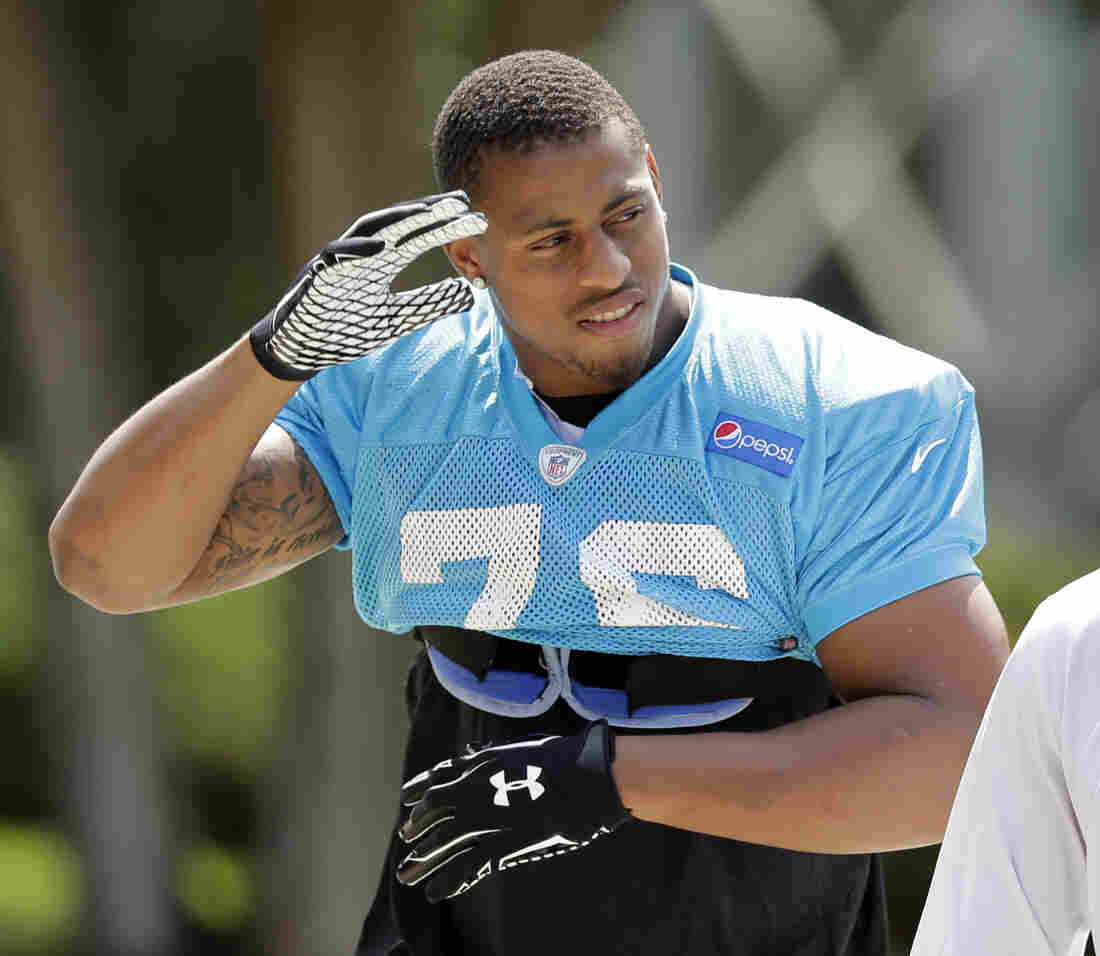 Carolina Panthers' Greg Hardy waves to fans as he arrives for an NFL football practice in Charlotte, N.C., Sept. 11, 2014.