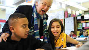 New York City Schools Chancellor Carmen Farina speaks with students Carlos Cruz and Lluvia Hernandez while visiting a school in Brooklyn earlier this year.