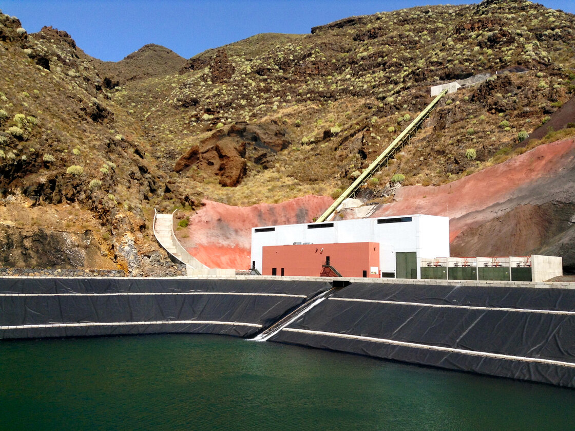 On days with little wind, water stored in El Hierro's upper reservoir is released through a pipe that cuts through the rocky hillside, falling through turbines and into this lower lake, for storage. On days with surplus wind energy, this water is pumped up the mountain to the mountaintop lake, for storage.