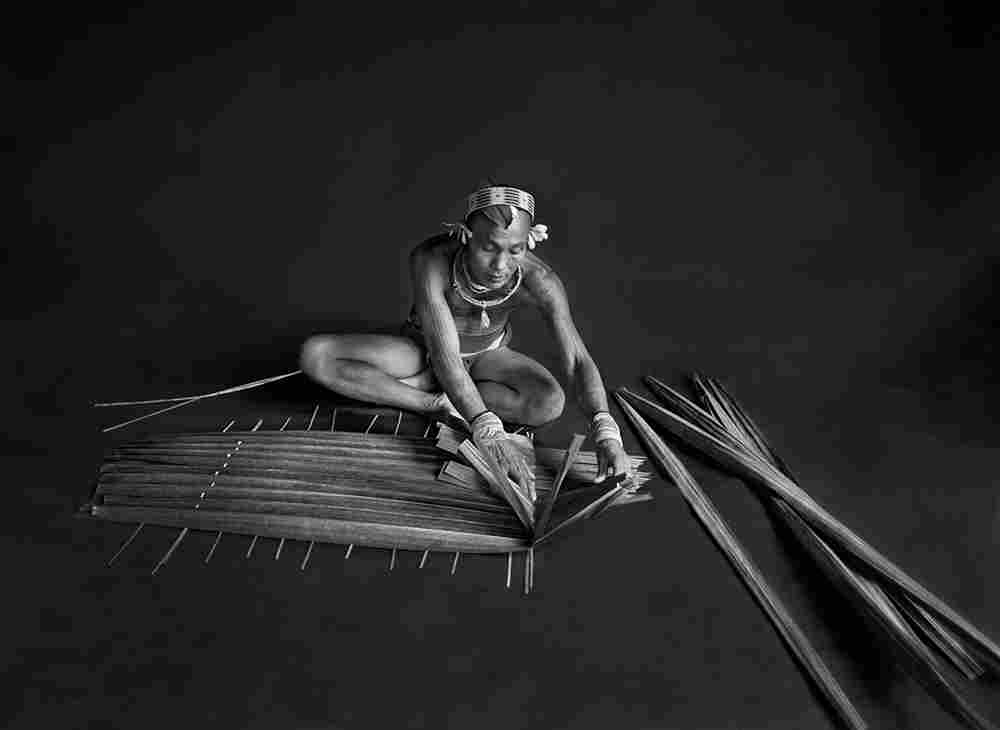 Teureum, a shaman for the Mentawai clan in West Sumatra, Indonesia, is preparing a filter for sago, a starch extracted from the sago tree, using the tree's leaves. 2008.