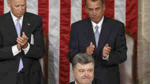 Ukrainian President Petro Poroshenko, joined by Speaker of the House John Boehner and Vice President Joe Biden,  acknowledges lawmakers' applause after addressing a joint meeting of Congress.