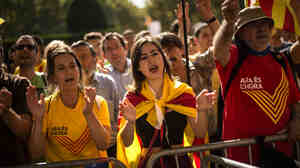 Pro-independence demonstrators shout slogans outside the Catalan parliament on Friday in Barcelona, Spain. The Catalan parliament has approved rules for a self-determination referendum — which would violate the Spanish constitution.