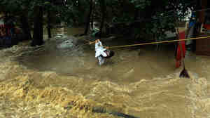 An Indian Kashmiri man in Srinagar uses a rope to cross over floodwaters in early September.