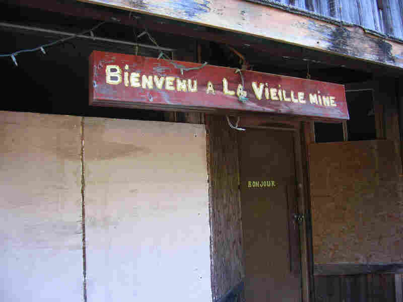 "A sign on an old store reads ""Bienvenu a la Vieille Mine,"" or ""Welcome to the Old Mine."""