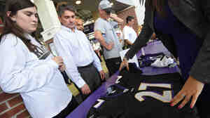 "Baltimore Ravens fans exchange the jersey of the team's former running back Ray Rice at M&T Bank Stadium Friday. ""He should have been the man here and backed away"" instead of hitting his fiancee, a female fan says."