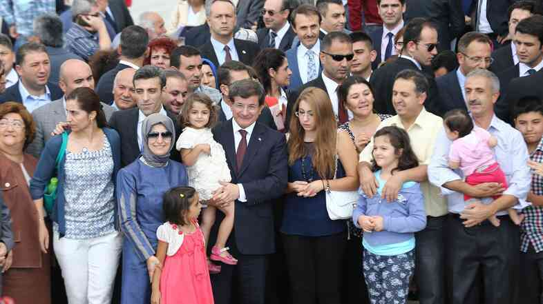 Prime Minister Ahmet Davutoglu, center, poses with dozens of freed Turkish hostages at the Esenboga Airport in Ankara Saturday. The group was held by militants in northern Iraq for more than three months.