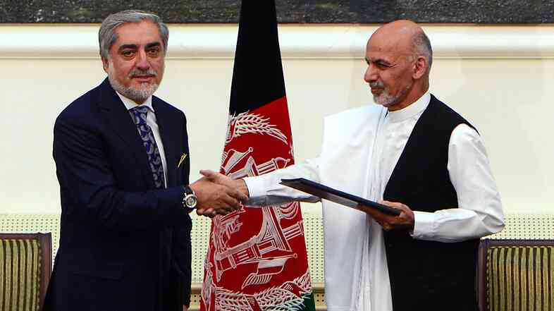 Afghan presidential candidates Abdullah Abdullah, left, and Ashraf Ghani Ahmadzai shake hands after signing a power-sharing pact in Kabul Sunday. The first vote in the election was held in April; a runoff followed in June.