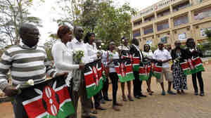 Survivors and relatives of victims carry Kenya's national flags on the anniversary of last year's deadly attack on the Westgate shopping mall in Kenya's capital of Nairobi.