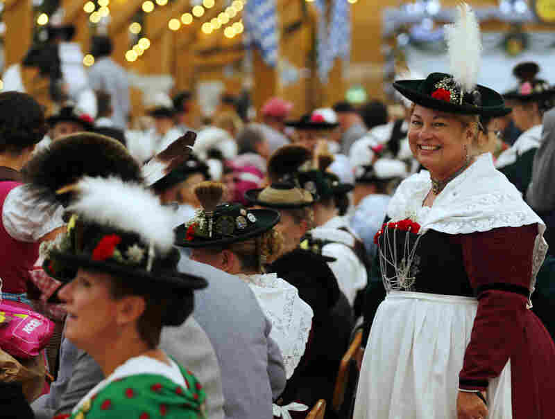 People in traditional Bavarian clothes take a break after the Oktoberfest parade in Munich.