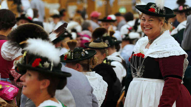 People wearing traditional Bavarian clothes take a break after the Oktoberfest parade in Munich Sunday. Millions of beer drinkers from around the world will visit the Bavarian capital over the next two weeks for the festival.