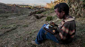 A boy plays with a solar-powered computer tablet on Mount Wenchi, Mirab Shewa zone of the Oromia region of Ethiopia.