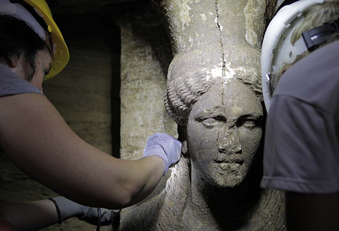 Archaeologists inspect a female figurine inside a recently discovered, fourth-century B.C. tomb, in the town of Amphipolis, northern Greece on Sept. 7. The occupant of the tomb is unknown, but there's speculation that it could be someone who was closely linked to Alexander the Great. (c) Greek Culture Ministry/AP