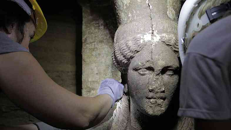 Archaeologists inspect a female figurine inside a recently discovered, fourth-century B.C. tomb, in the town of Amphipolis, northern Greece on Sept. 7. The occupant of the tomb is unknown, but there's speculation that it could be someone who was closely linked to Alexander the Great.