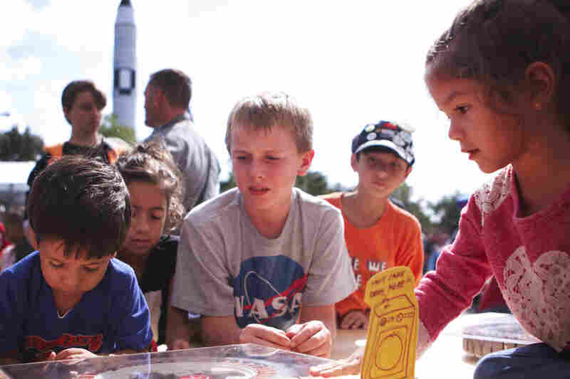Kids discover the power of magnets at World Maker Faire in Queens, N.Y. Oh, yeah: That's a real rocket in the background.