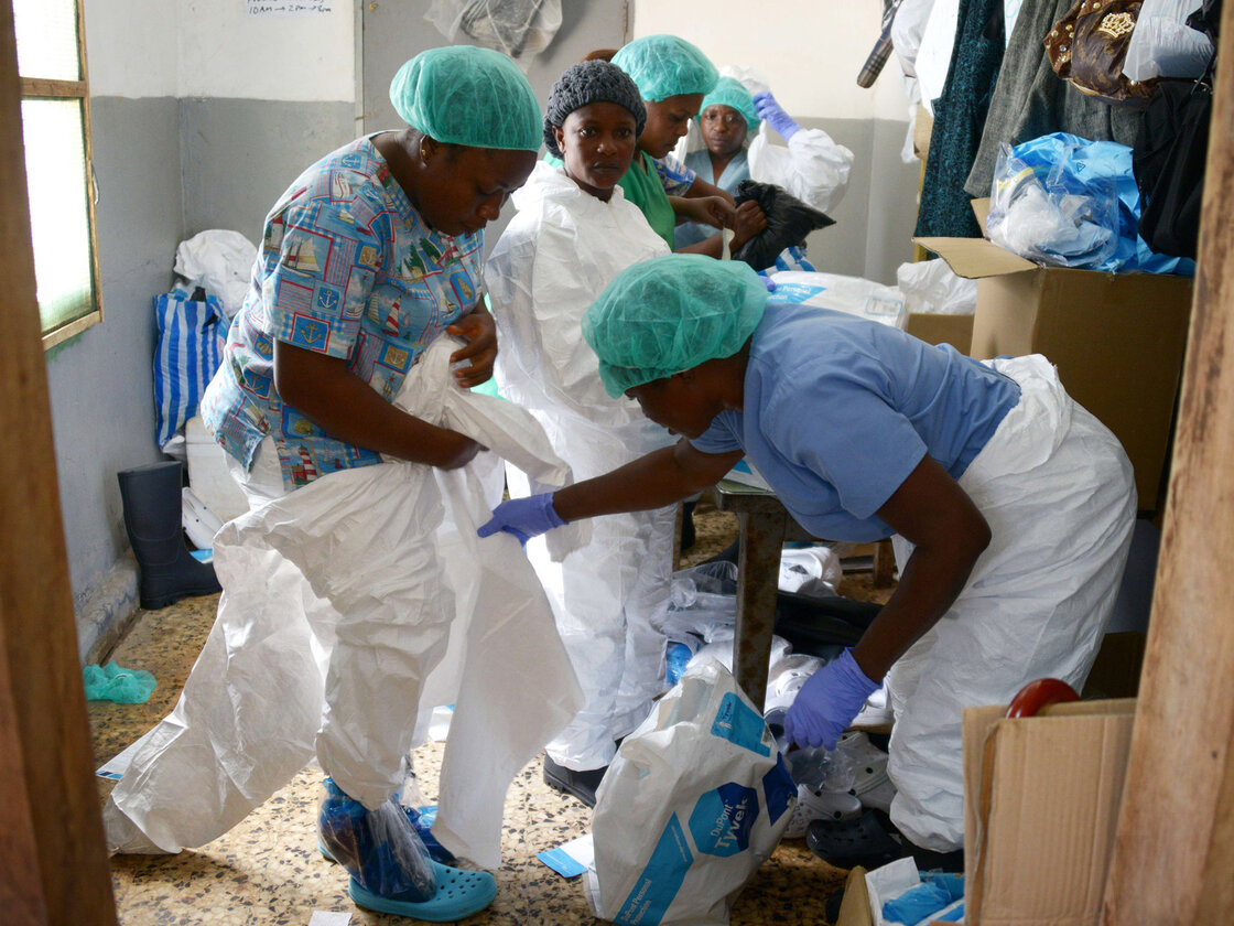 Medical workers in Monrovia, Liberia, put on their protective suits before treating Ebola patients