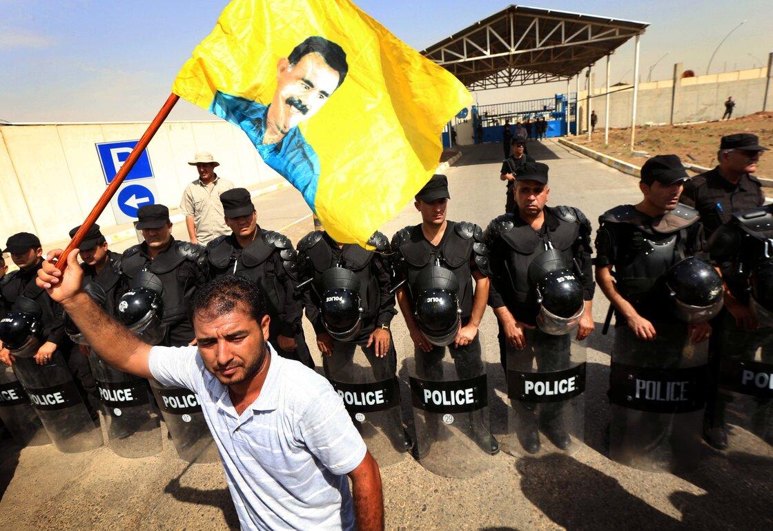 Los EE.UU. tienen diferentes políticas hacia diferentes grupos kurdos.  Los EE.UU. trabaja en estrecha colaboración con los kurdos iraquíes, cuyos policías formar una línea en esta foto.  Pero los EE.UU. etiquetas un grupo militante kurdo de Turquía, el PKK, una organización terrorista.  A PKK olas partidario de una bandera amarilla de líder del grupo.  Tres milicianos kurdos independientes han estado combatiendo al grupo que se autodenomina Estado Islámico.
