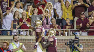 Florida State fans cheer Rashad Greene after a 74-yard touchdown pass in the fourth quarter of an NCAA college football game against Clemson in Tallahassee, Fla., on Sept. 20. In college sports, African-American student athletes and white student audiences are the norm. Commentator Frank Deford asks why this dynamic does not make us more squeamish.