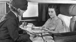 The good old days: A flight attendant serves coffee and sandwiches to a passenger on board an American Airlines flight, circa 1935.