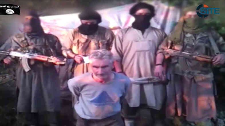This still image from video published on the Internet on Wednesday by a group calling itself Jund al-Khilafah, or Soldiers of the Caliphate, shows members of the group standing behind French mountaineer Herve Gourdel just before beheading him.