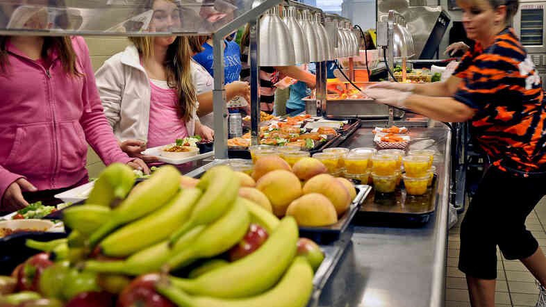 Students are given healthy choices on a lunch line at Draper Middle School in Rotterdam, N.Y., in 2012. To keep students from tossing out the fruits and vegetables they're served, researchers say it helps to give them a choice in what they put on their trays.