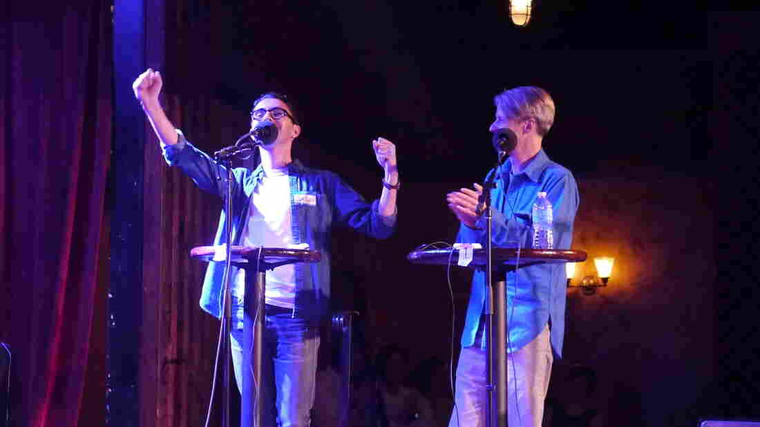 John Cameron Mitchell (right) and contestant Jordan Shavarebi celebrate a victory during their Ask Me Another Challenge.