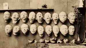 Plaster casts taken from soldiers' mutilated faces (top row), new sculpted faces (bottom row), and final masks (on the table) sit in the studio of Anna Coleman Ladd in 1918.