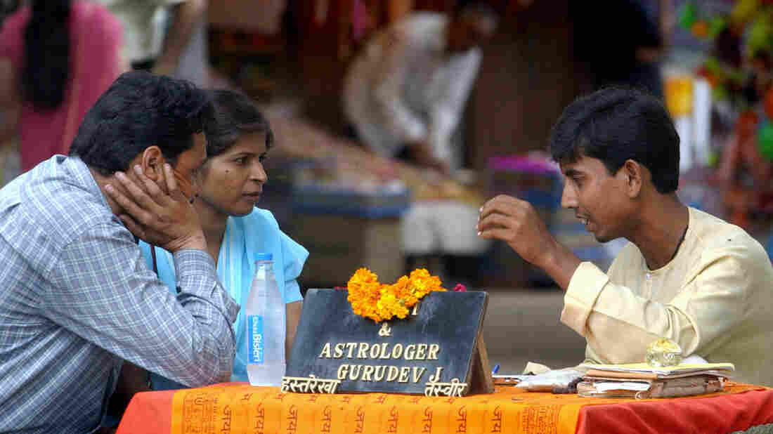 An unidentified Indian astrologer talks with a couple at a pavement booth near a Hindu temple in New Delhi in 2003.