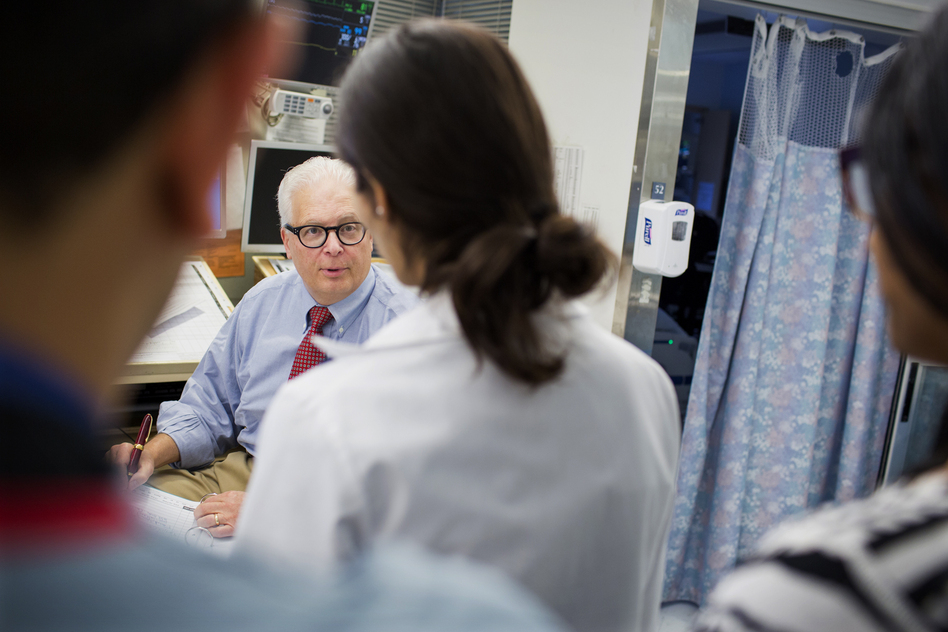Dr. Allan Ropper speaks with residents and fellows as they do rounds at the neuroscience intensive care unit at Brigham and Women's Hospital in Boston. (M. Scott Brauer for NPR)