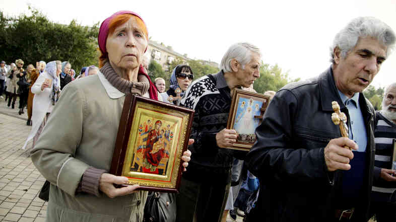 Ukrainians pray during a service supporting the self-proclaimed Donetsk People's Republic in front of an occupied administration building in Donetsk, Ukraine. A ceasefire has been shaky and many separatists say their goal is still full independence from Ukraine.