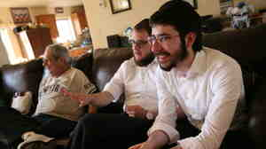 Chabad rabbinical students Zalman Refson (right) and Yaakov Kaplan sit alongside a Jewish resident of Taylor, Ariz. As roving rabbis, the duo recently went to about 40 tiny towns and cities across Arizona, meeting rural Jews along the way.