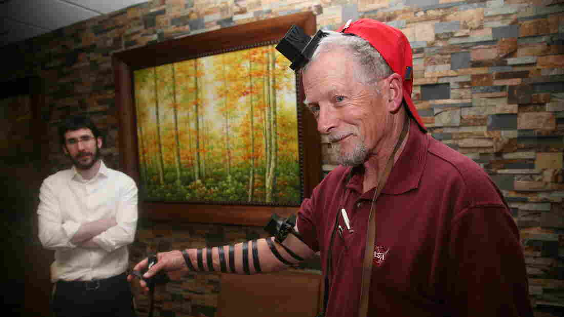 """Rabbinical student Zalman Refson (left) recently traveled across Arizona as part of a duo of """"roving rabbis,"""" working to help rural Jews reconnect with their faith. Here, he helps Aaron Bornstein prepare for traditional prayer by laying tefillin, small leather boxes containing parchment inscribed with verses from the Torah that are fastened to the arm and forehead with leather strips."""