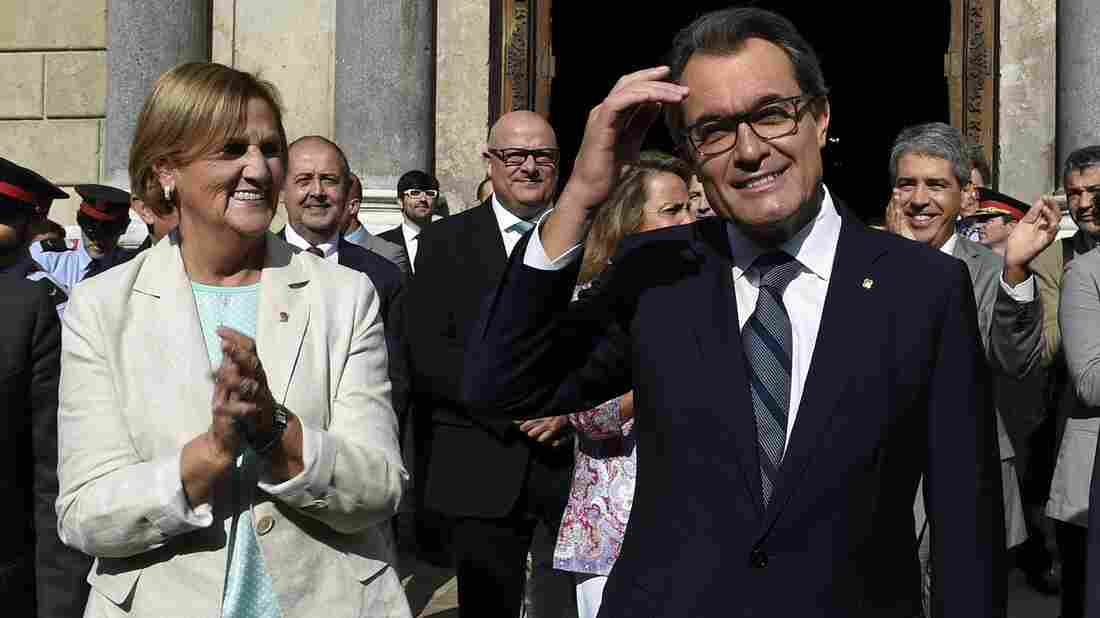 President of Catalonia's regional government Artur Mas acknowledges cheers Saturday after signing a law setting a Nov. 9 vote on independence. At left is the president of the Catalan Parliament, Nuria de Gispert.