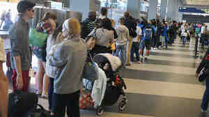 Travelers lined up Friday to reschedule flights at Chicago's O'Hare International Airport after the region's air traffic control was sabotaged. More flights are resuming Saturday, but hundreds were also canceled.
