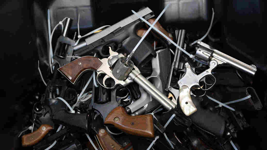 Surrendered handguns are piled in a bin during a gun buyback event in Los Angeles on May 31, 2014.