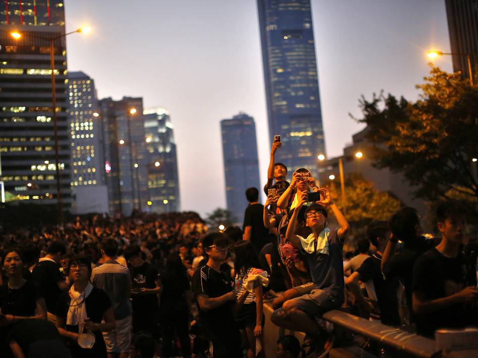 Protesters take pictures with their mobile phones on Monday as they block the main street to the financial Central district, outside the government headquarters in Hong Kong. (Carlos Barria/Reuters/Landov)