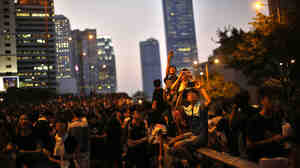 Protesters take pictures with their mobile phones on Monday as they block the main street to the financial Central district, outside the government headquarters in Hong Kong.