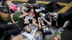 People check their phones at a pro-democracy demonstration in Hong Kong on Monday.