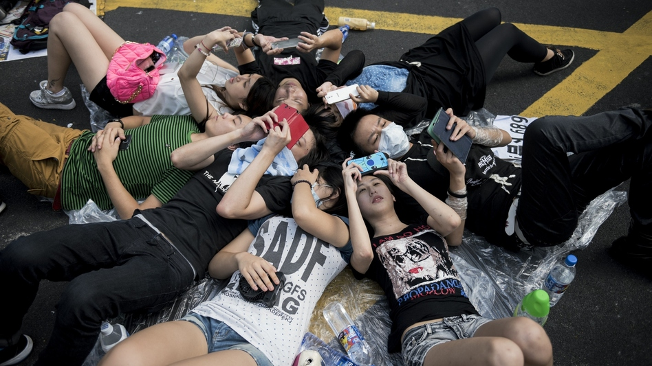People check their phones at a pro-democracy demonstration in Hong Kong on Monday. (Alex Ogle/AFP/Getty Images)