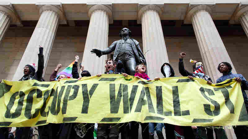 Occupy Wall Street demonstrators stand and cheer in front of the George Washington statue on Wall Street. Millennials were heavily involved in this movement.