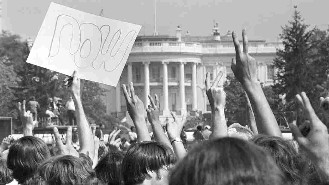"""Anti-Vietnam War demonstrators hold up signs and raise their hands toward the White House in a protest. The term """"baby boomers"""" stuck for this generation because of their tumultuous youth."""