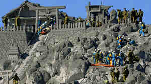 A photo taken from a Kyodo News helicopter shows Japan's Self-Defense Forces personnel rescuing climbers who were in critical condition near the top of Mt. Ontake Monday, before rescue operations were suspended.