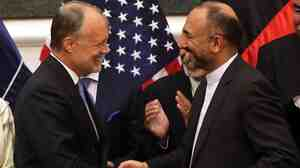 Afghan National Security Advisor Hanif Atmar (right) and U.S. Ambassador to Afghanistan James Cunningham exchange documents after signing the bilateral security agreement, with Afghan President Ashraf Ghani (rear, left) and Chief Executive Abdullah Abdullah in the background.