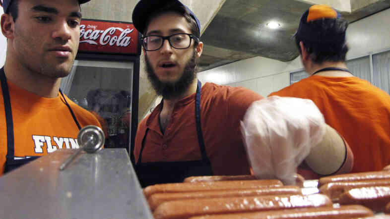 University of Illinois student Stanley Dayan, left, and Chabad Jewish Center employees Mordy Kurtz, center, and Yosef Peysin work at the center's kosher food stand in 2013 at the university's State Farm Center basketball arena in Champaign, Ill.