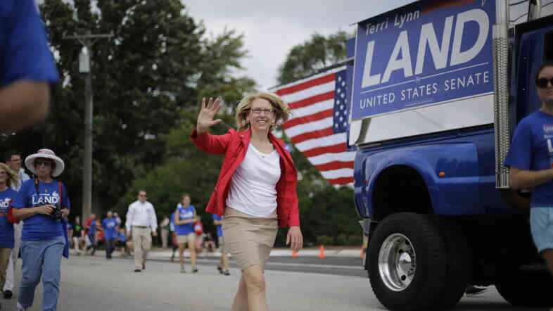 Terri Lynn Land walks in the Labor Day Parade in Romeo, Mich. on Sept. 1, 2014. Land has had some public appearances like this one, but overall is running a low-key race in the state.