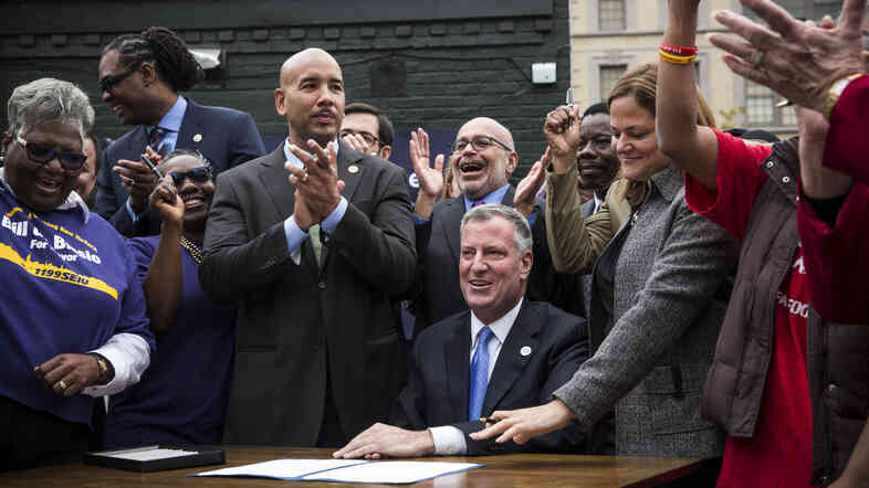 New York City Mayor Bill de Blasio signs an executive order raising the city's living wage law Tuesday. The move will require some employers to pay their employees between $11.50 and $13.13 an hour, depending on whether the employee receives benefits.