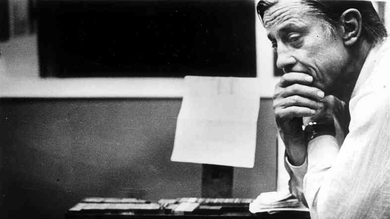 "Ben Bradlee, then-executive editor of The Washington Post, looks at the front page of the newspaper, headlined ""Nixon Resigns,"" in the composing room on Aug. 8, 1974."