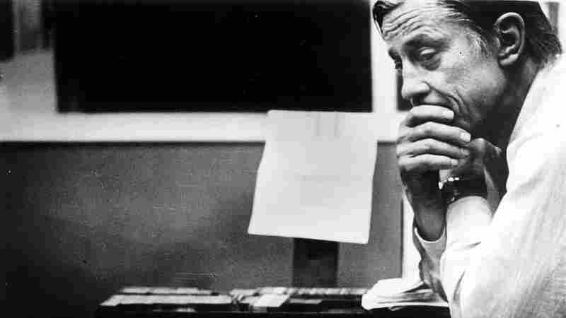 """Ben Bradlee, then-executive editor of The Washington Post, looks at the front page of the newspaper, headlined """"Nixon Resigns,"""" in the composing room on Aug. 8, 1974."""